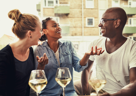 dining out: Friends out dining, multi ethnic concept, laughing and having a good time Stock Photo