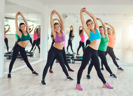 Teamwork of group of women doing exercise and looking at camera.