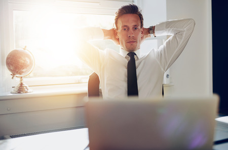 paralegal: White male executive working overtime at office, looking at his laptop while leaning back on his chair