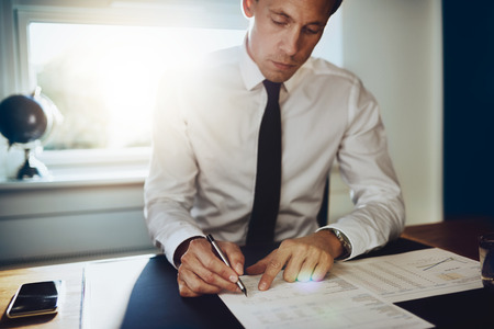 paralegal: Executive male working at desk looking at documents and accounts holding a pen and looking concentrated and serious