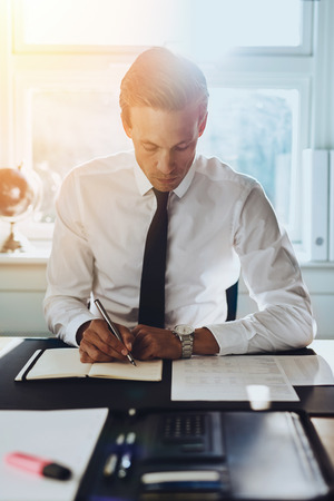 White male executive working at office at his desk with accounts and documents, looking in a black note book