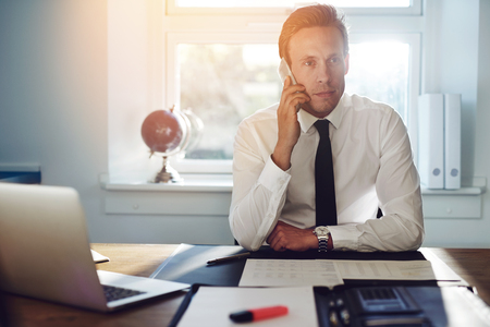 Young white business man talking on the phone, sitting at desk wearing suit and tie Stock Photo