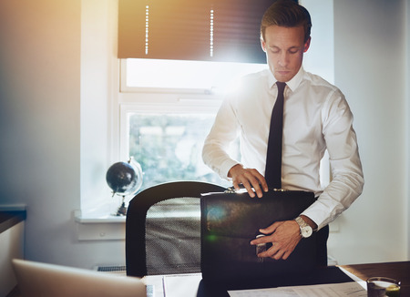 leather briefcase: Business man with briefcase at office standing at desk looking serious