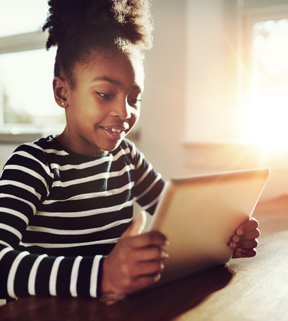 learning online: Close up Pretty Black Girl Playing Online Games on her Tablet Computer with Happy Facial Expression. Stock Photo