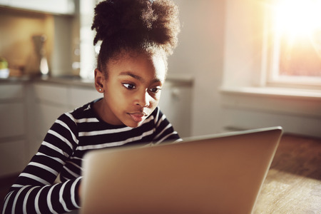 trendy girl: Pretty Black Teen Girl Watching a Movie on her Laptop Computer Seriously at Home. Stock Photo