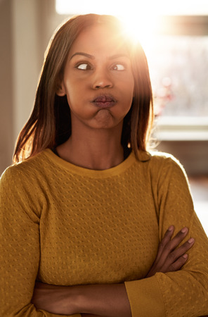 perplex: Young woman making a goofy face squinting and puffing out her cheeks in exasperation as she stands with folded arms in front of a bright window with sun flare Stock Photo