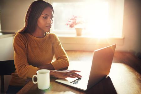Prachtige zwarte vrouwelijke zitten aan tafel met kop en typen op een laptop met felle zon komt door raam