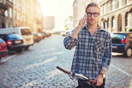 hombres jovenes: Un retrato de un hombre joven hermoso que habla en su teléfono celular en la ciudad