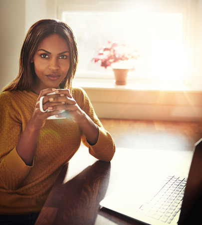 introspective: Beautiful Black woman in yellow sweater sitting at table holding coffee cup next to laptop with bright light coming through window