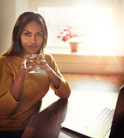 Schöne schwarze Frau im gelben Pullover sitzen am Tisch Kaffeetasse neben Laptop mit hellem Licht durch das Fenster kommt Lizenzfreie Bilder
