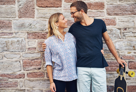 three quarter: Three Quarter Shot of a Sweet Lovers Smiling Each Other Against Concrete Wall Background.