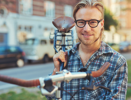 specs: Man carrying his bike. City Lifestyle. Looking into camera Stock Photo