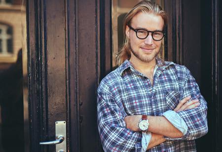 beau jeune homme: Heureux jeune homme. Portrait de beau jeune homme en chemise d�contract�e bras de tenue travers� et souriant debout sur fond gris Banque d'images