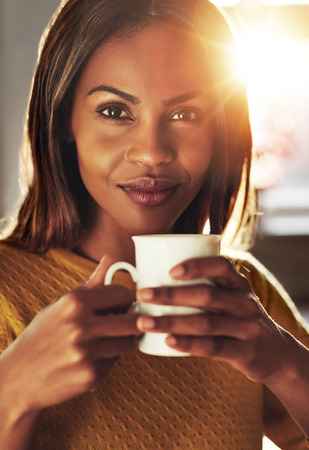 amiable: Attractive black woman enjoying an energising cup of coffee holding the mug in her hands as she looks at the camera with a quiet friendly smile, sun flare behind Stock Photo
