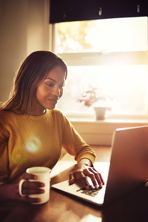 Happy gorgeous adult single female sitting near bright sunny window typing on her laptop computer and holding coffee cup Фото со стока
