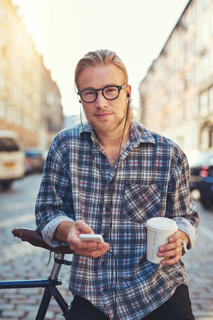 people   lifestyle: Portrait of cool young man living in the city, holding a cup of coffee and his cellphone