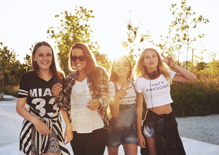 Group of girls laughing and posing, outside on a summer day, sun flare