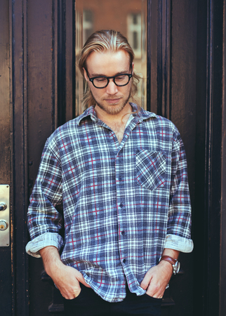 long depression: Thoughtful Man with blonde hair and glasses wearing a blue shirt
