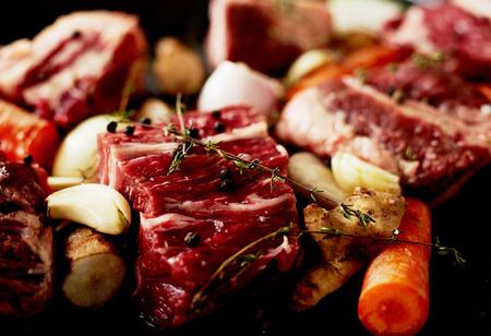 carne cruda: Piezas de ternera de ternera con zanahorias ajo y romero listo para cocinar