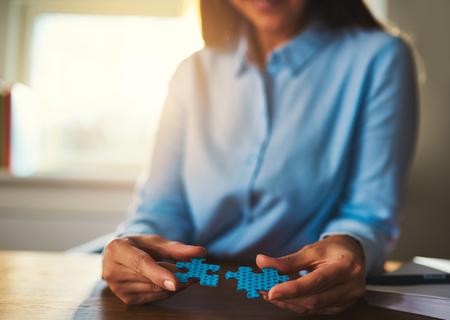 ability: Business woman connecting puzzles, closeup of hands, success concept