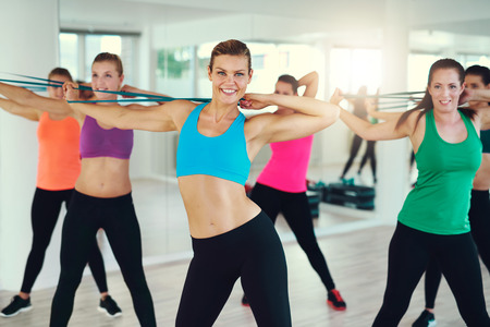 synchronously: Group of young women stretching arms in studio