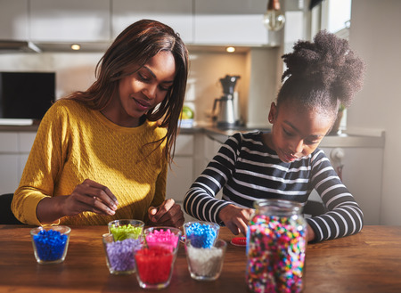 afro girl: Child and parent sitting and creating color beaded crafts on wooden table in kitchen with various jars in front of them