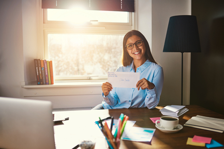 Business woman holding a letter to send while smiling at camera