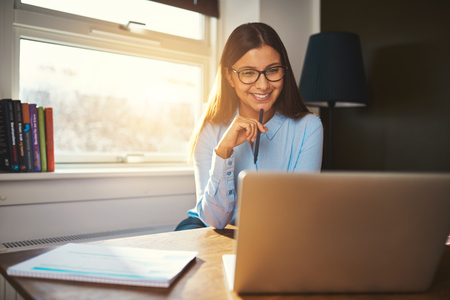 Business woman working at office looking at laptop with a pen in her hand