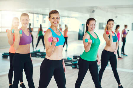synchronously: Young women working out using dumbbells