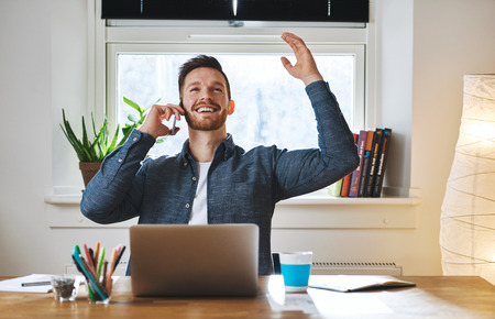Successful entrepreneur looking happy sitting at desk with arms over head