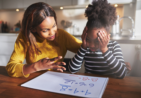 helping children: Mother learning her daughter to calculate elementary school work