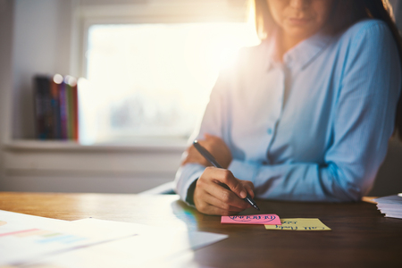 Closeup business woman writing notes on a post it Stock Photo