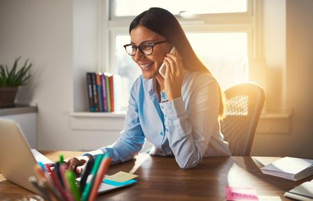 Bedrijfsvrouw die aan laptop het glimlachen het spreken op telefoonzon werken die door venster komen Stockfoto