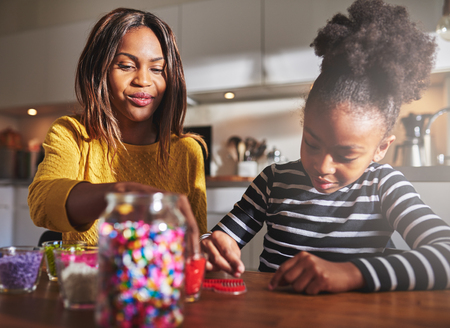 babysitting: Cute young girl in striped shirt making a red bead craft with woman in kitchen with sunlight beaming in across the background