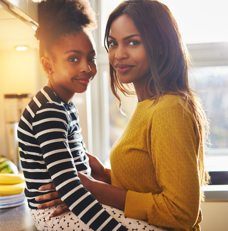 happy african: Black woman and her daughter smiling at camera looking happy