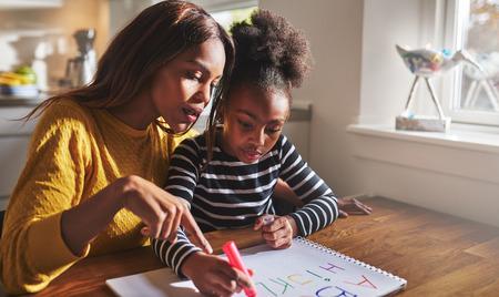 familia cenando: Niña aprendiendo negro para leer el aprendizaje del alfabeto Foto de archivo