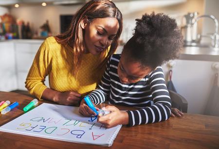 mujer hijos: Ni�a que aprende el alfabeto con letras de colores Foto de archivo