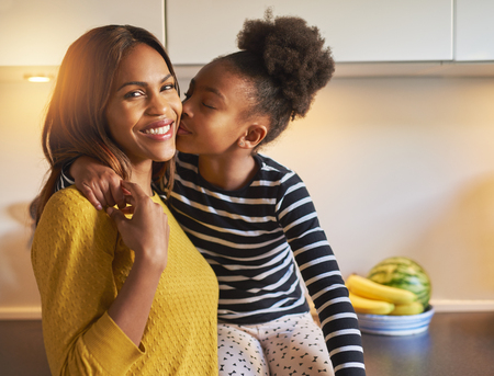 woman with camera: Black mom and daughter loving each other woman smiling at camera