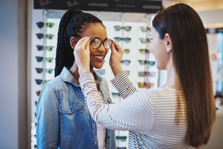 joven mujer afroamericana selección de un par de marcos para gafas sonriendo siendo asistida por un optometrista en la tienda Foto de archivo