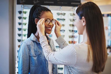 Uśmiechnięta młoda kobieta Afroamerykanów wybierając parę ramek dla jej okulary jest wspomagany przez optometrist w sklepie Zdjęcie Seryjne