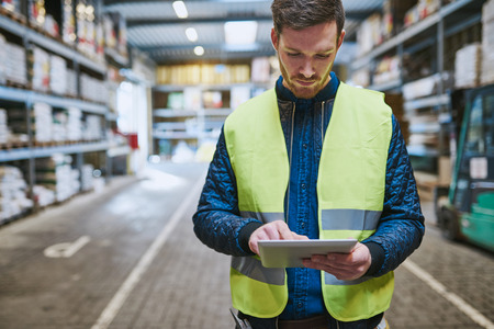 ouvrier: Jeune homme regardant détails de la commande sur une tablette comme il les magasins dans un entrepôt de matériel de fournitures, de près du haut du corps