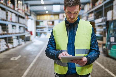 trabajadores: Joven mirando hacia arriba detalles de la orden en una tableta que hace la compra en un almacén de hardware para los suministros, primer parte superior del cuerpo