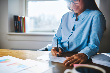 selfemployed: Selective focus close up of cheerful young self-employed woman wearing glasses and blue shirt at desk writing on form next to cup of coffee and booklets