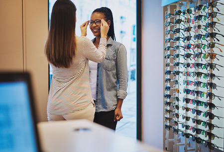 Optometrist helping a young African woman in her store to select a pair of frames for her eyeglasses Imagens