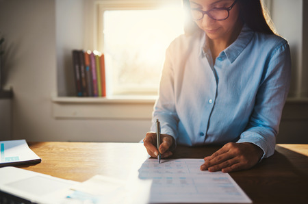 low blouse: Single woman in blue blouse working at desk on paperwork in home office with sunlight over her shoulder through window