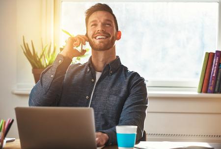 自信を持って起業家満足度の大喜びの笑顔で空気を見上げて彼の机で働いている間携帯電話でチャット