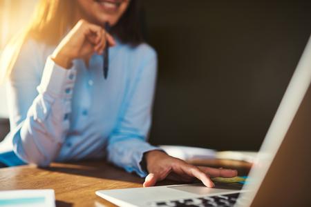 la mujer del primer usando la computadora portátil que sostiene la pluma, la mitad del cuerpo visible