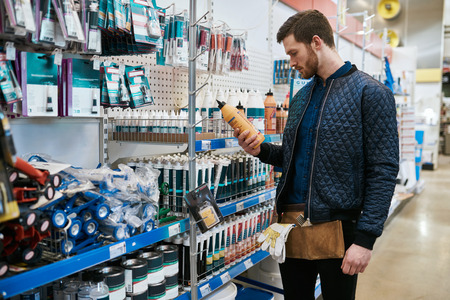 homeowner: Young handyman or DIY homeowner in a store standing selecting a product in the hardware department and reading the label Stock Photo