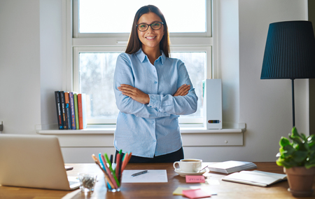 business management: Confident young businesswoman with a friendly smile standing behind her desk in a home office with folded arms smiling happily at the camera