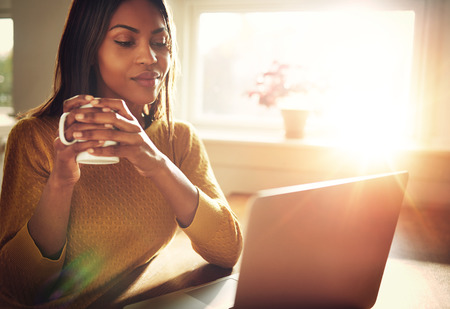 flare: Adult woman smiling sitting near bright window while looking at open laptop computer on table and holding white mug